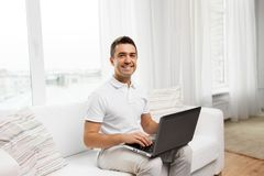 Happy man with laptop computer at home stock image
