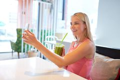 Woman with smartphone taking selfie at restaurant Royalty Free Stock Images