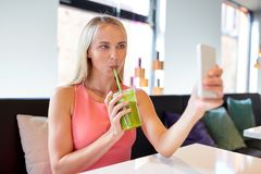 Woman with smartphone taking selfie at restaurant Royalty Free Stock Photography