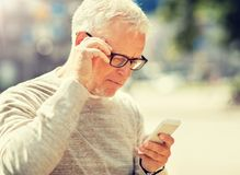 Senior man texting message on smartphone in city royalty free stock photos
