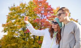 Couple taking selfie by smartphone in autumn park stock image