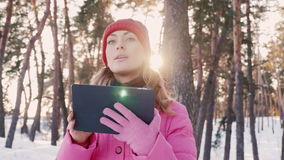 Technology popogayut people. Young woman enjoys the tablet with the program GPS navigation in snowy woods. Young woman looking for the right way, using a tablet stock video