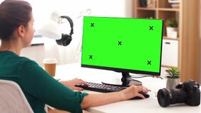 Woman with green screen on computer at home. Technology, post production and people concept - woman with chroma key green screen on computer drinking takeaway stock video footage