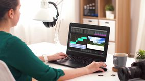Woman with video editor program on laptop at home stock video