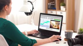Woman with video editor program on laptop at home stock footage
