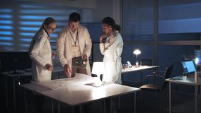 Technology Research Facility: Multiracial Electronics Development Engineers in white coats working in lab with. Motherboard and control electronics scheme. They stock video footage