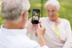 Old woman photographing man by smartphone in park. Technology, retirement and old people concept - happy smiling senior couple with smartphone photographing in Royalty Free Stock Image