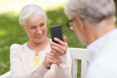 Old woman photographing man by smartphone in park. Technology, retirement and old people concept - happy smiling senior couple with smartphone photographing in Royalty Free Stock Photos