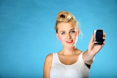 Technology. Retro style happy girl offering mobile phone Stock Image