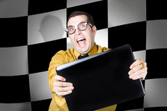 Technology salesman selling laptop computers. Overexcitable technology sales man selling laptop computers with winning deals. Finish flag background Royalty Free Stock Images
