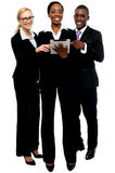 Technology savvy business team using tablet pc Stock Photography