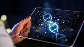 Hand with virtual dna projection on tablet screen
