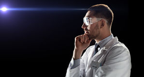 Doctor or scientist in lab coat and safety glasses. Technology, science, and people concept - male doctor or scientist in white coat and safety glasses over Royalty Free Stock Image