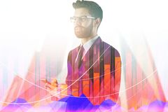 Technology and stock concept. Attractive young european businessman using smartphone on abstract city background with forex chart and copy space. Technology and stock photography