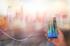 Technology and stock concept. Hand holding smartphone with abstract forex chart on blurry city background. Technology and stock concept. Double exposure Stock Photography
