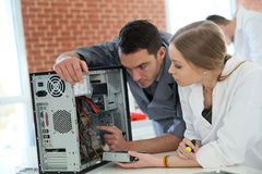 Technology student learning from teacher. Teacher with student in technology repairing computer royalty free stock photo
