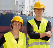 Technology students. Two Engineering students posing in front of a huge freight vessel during their technological internship in a harbor Stock Photography
