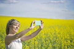 Technology, summer holidays, vacation and people concept - hands of womantaking selfie by smartphone on field. Technology, summer holidays, vacation and people stock images