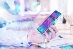 Technology and trade concept. Hand holding smartphone with business chart on abstract background with forex diagram. Technology and trade concept. Double Stock Photography