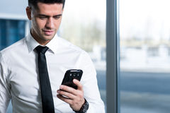 Technology usefulness at work. Smartly clothed businessman looking at his mobile phone Stock Photos