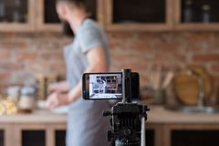 Technology video stream phone camera man kitchen. Modern technology for video streaming. phone camera on tripod. equipment and tools used by food blogger. man royalty free stock photo