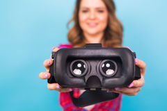 Technology, virtual reality, entertainment and people concept - Girl give virtual reality goggles. Stock Photography