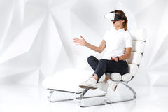 Technology, virtual reality, entertainment and people concept - happy young woman with virtual reality headset sits on a. White armchair in a room with white Royalty Free Stock Images