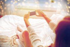 Woman photographing with smartphone in bet at home. Technology, winter, augmented rality and people concept - young woman in bed holding smartphone with black Stock Image