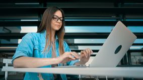 IT Technology Work. Beautiful student girl wears glasses and jeans scirt works with laptop computer near modern building wall outdoor, slowmotion stock footage
