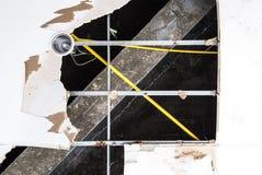 Techo dañado con el tubo de la lámpara y la estructura eléctricos del metal Imagenes de archivo