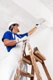 Techo de la pintura del pintor con el rodillo de pintura Imagen de archivo libre de regalías