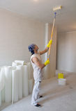 Techo de la pintura del trabajador con el rodillo de pintura fotos de archivo