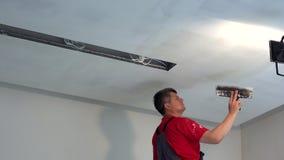 Techo spackling del hombre del yesero con masilla Trabajos de acabado del nuevo apartamento almacen de video