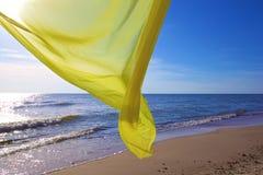 Tecido amarelo que voa sobre o mar Fotos de Stock