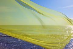 Tecido amarelo que voa sobre o mar Imagens de Stock Royalty Free