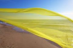 Tecido amarelo que voa sobre o mar Fotografia de Stock Royalty Free