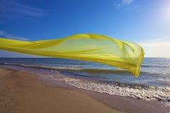Tecido amarelo que voa sobre o mar Fotos de Stock Royalty Free