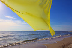 Tecido amarelo que voa sobre o mar Foto de Stock Royalty Free