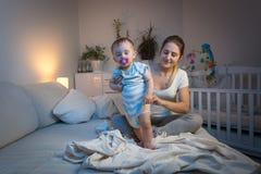 Tecidos em mudança de inquietação novos da mãe a seu bebê sonolento antes de ir dormir imagem de stock