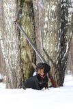 Teckel et fusil de chasse noirs près de l'arbre de bouleau dans la forêt d'hiver Photographie stock