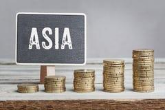 Tecken Asien med tillväxtmyntbuntar Arkivfoto