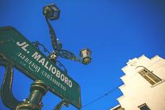 Tecken av den Malioboro gatan och en forntida byggnad Arkivbild