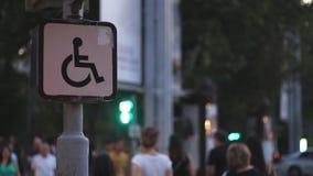 Tecken av ett sammanträde för rörelsehindrad person på en rullstol mot bakgrunden av suddigt gå folk internet för begreppsanslutn lager videofilmer