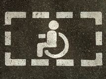 Tecken av handikappade personer rullstol på asfalt, parkeringsplatser för rörelsehindrade besökare arkivfoton