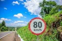 Tecken av 80 kilometer per timmegräns på bakgrunden av den lilla kullen som täckas med gräs, den långa vägen som går till horison royaltyfria foton