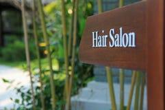 Tecken av riktningen till hårsalongen i ett hotell, en semesterort och en brunnsort Arkivfoton