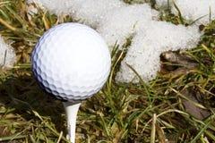 Tecken av våren, golfboll på utslagsplats med snö Arkivfoton