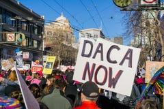Tecken för `-Daca nu ` som bärs av en deltagare på mars för kvinna` s fotografering för bildbyråer