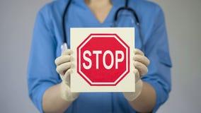 Tecken för doktorsinnehavstopp som varnar om sjuklig livsstil, skadliga vanor arkivbilder