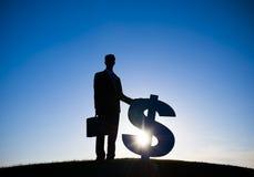 Tecken för dollar för tillbaka Litaffärsman hållande Royaltyfria Foton